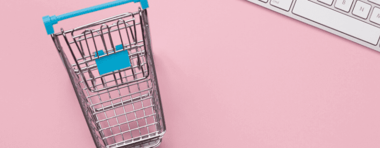 Flatlay of mini shopping cart placed beside white keyboard on a pink surface