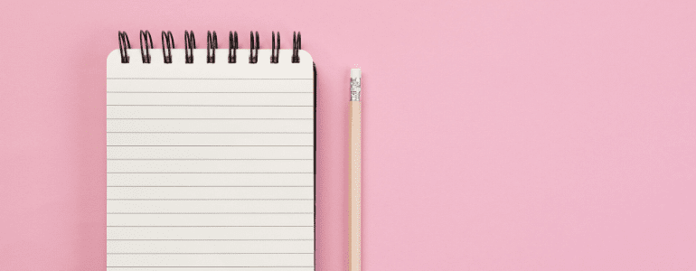 Notebook and pencil against pink background