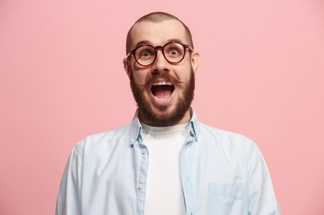 Surprised-looking bearded man wearing blue shirt against pink background