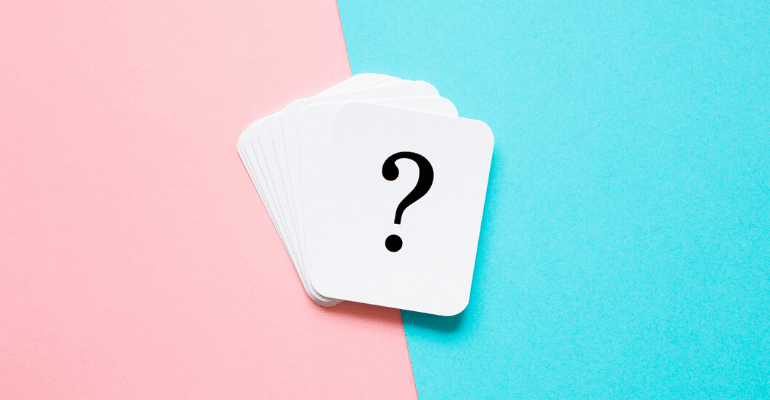 Deck of cards with question mark on top card against pink and blue background