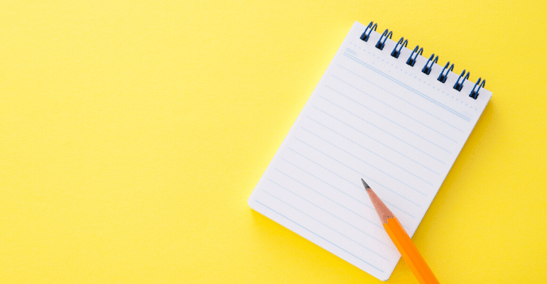 Notepad and pencil against yellow background