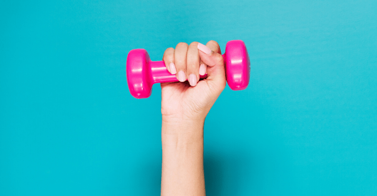 Hand holding a pink dumbbell against turquoise background
