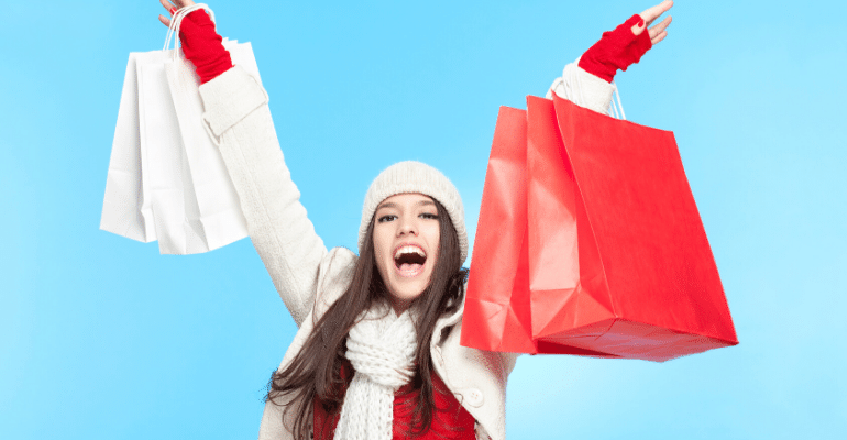Woman in winter attire carrying shopping bags