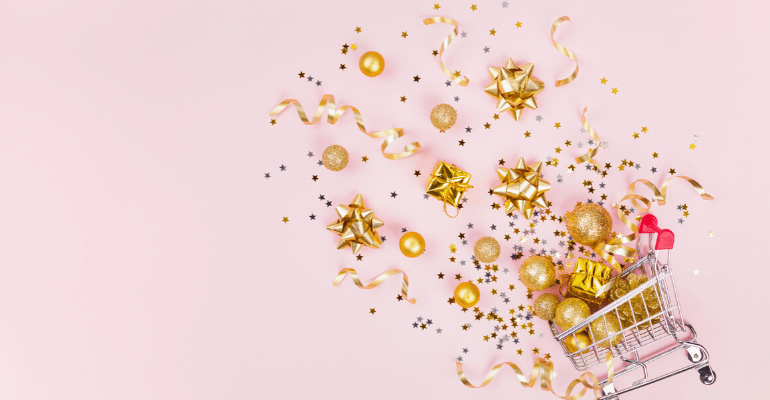 Gifts and confetti spilling out of a shopping cart against pink background