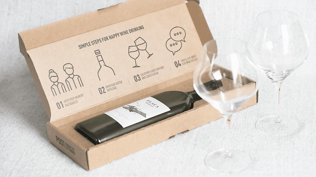 Wine bottle in cardboard box. Two empty wine glasses beside it.